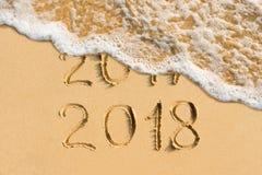 新年概念2018年和2017手写在海滩 免版税库存照片
