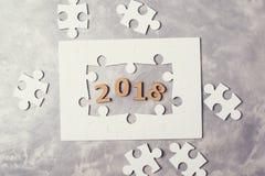 新年概念2018年 在灰色具体背景的七巧板 免版税图库摄影