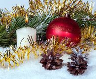 新年球、蜡烛和冷杉球果在闪亮金属片和枝杈中 免版税库存照片