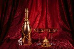 新年瓶香槟和蜡烛、玻璃和狗在红色背景 免版税库存照片