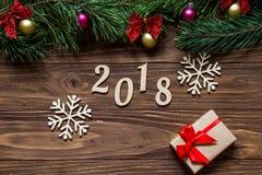 新年的原始的博览会与两美丽的雪花和一个礼物盒的2018年在木背景的中心 库存图片