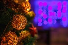 新年的玩具和冷杉分支在紫罗兰色轻的背景 免版税图库摄影