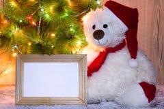 新年的,圣诞节熊坐在与一个木制框架大模型的一棵杉树下的照片的或文本 免版税库存图片