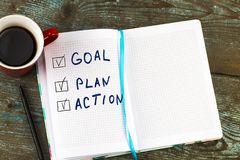 新年目标,计划,行动-发短信在与咖啡的笔记薄 免版税图库摄影