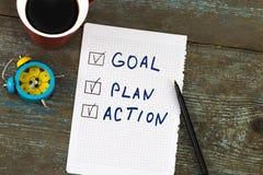 新年目标,计划,行动-发短信在与咖啡的笔记薄 免版税库存照片