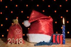 新年红色帽子、一个袋子与礼物,一个蓝色蜡烛和小珠机智 免版税库存图片