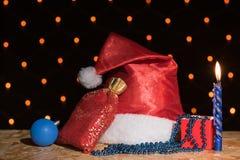 新年红色帽子、一个袋子与礼物,一个蓝色蜡烛和小珠机智 免版税库存照片