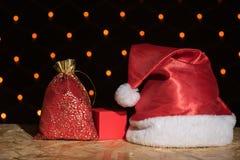 新年红色帽子,与一件礼物的一个袋子在bac的一张木桌上 库存照片