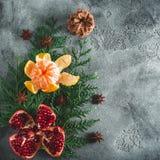 新年结构的可口石榴石,普通话 桂香和茴香在黑暗的背景 假日食物概念,拷贝空间 平面 图库摄影