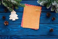 新年问候的空间 纸近的圣诞节玩具和云杉的分支在蓝色木背景顶视图大模型 免版税库存照片