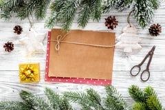 新年问候的空间 纸近的圣诞节玩具和云杉的分支在轻的木背景顶视图大模型 免版税库存照片