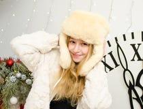 新年,一个帽子帽子的美丽的年轻白肤金发的妇女有在时钟背景的耳朵的 图库摄影