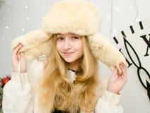 新年,一个帽子帽子的美丽的年轻白肤金发的妇女有在时钟背景的耳朵的 免版税库存图片