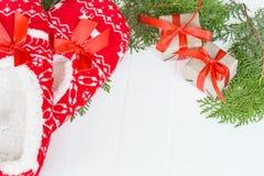 新年,在白色木背景的圣诞节拖鞋 在杉木分支附近 滑稽,滑稽,舒适 免版税图库摄影