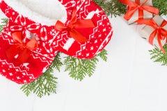 新年,在白色木背景的圣诞节拖鞋 在杉木分支附近 滑稽,滑稽,舒适 免版税库存图片
