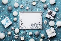 新年2018党背景 与圣诞节装饰、礼物盒、五彩纸屑和衣服饰物之小金属片的银色框架在葡萄酒蓝色桌上 免版税库存图片