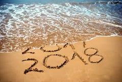 新年2018年是以后的概念-在海滩沙子的题字2017年和2018年,波浪包括数字2017年 新年2018年著名人士 免版税库存图片