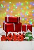 新年2018标志标志、圣诞树做用姜饼曲奇饼和有bokeh和透镜火光样式的红色礼物盒 免版税库存图片