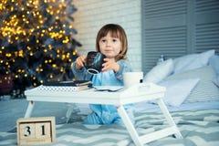 新年` s伊芙, 12月31日 睡衣的逗人喜爱的小女孩有在圣诞树附近的杯子的 免版税库存照片