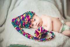 新年` s地精盖帽的新出生的婴孩在一条白色毯子放置 免版税库存图片