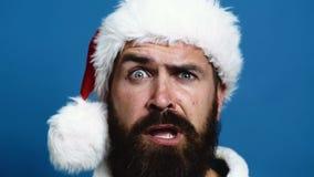 新年` s帽子的有胡子的人在蓝色背景做鬼脸 在蓝色背景的滑稽的圣诞老人 概念 股票录像