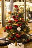 新年` s树,装饰用金黄和红色球、小珠和闪亮金属片 库存照片