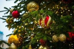 新年` s树,装饰用金黄和红色球、小珠和闪亮金属片 库存图片