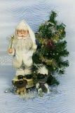 新年` s照片与圣诞老人和逗人喜爱的狗的贺卡在装饰的圣诞树背景  免版税库存图片