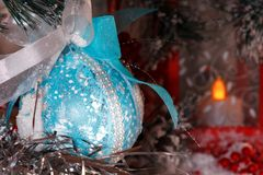 新年` s球在圣诞树的分支垂悬反对有一个蜡烛的一个红色灯笼 免版税库存照片