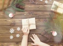 新年` s礼物,手,圣诞树分支与锥体,雪花 免版税图库摄影