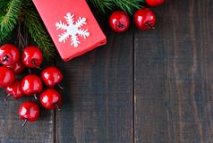 新年` s,圣诞节题材 礼物盒,在黑暗的木背景的莓果 免版税库存照片
