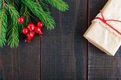 新年` s,圣诞节题材 礼物盒,绿色云杉的分支,在黑暗的木背景的莓果 免版税库存图片