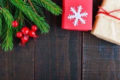 新年` s,圣诞节题材 礼物盒,绿色云杉的分支,在黑暗的木背景的莓果 库存图片