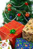 新年` s,在一棵装饰的圣诞树的背景的圣诞节礼物 图库摄影