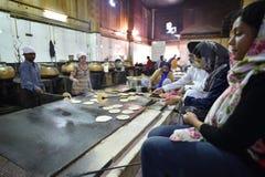 新德里,印度, 2017年11月23日:准备面包的人们在厨房里 免版税图库摄影