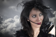 新性感的妇女纵向黑色面纱的在多云天空 库存图片