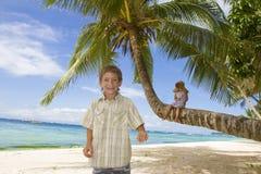 新愉快的孩子-男孩和女孩-在热带海滩backgrou 库存照片