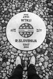 新戈里察斯洛文尼亚-戈里齐亚意大利:供以人员在站立在斯洛文尼亚和意大利之间的边界的牛仔裤和运动鞋的` s腿 库存图片