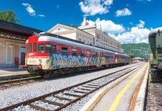 新戈里察,斯洛文尼亚:有街道画的红色火车在轨道站立在火车站 免版税库存图片