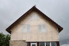 新房墙壁反对蓝天的门面绝缘材料 温暖与矿棉的屋顶或顶楼 免版税库存照片