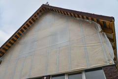 新房墙壁反对蓝天的门面绝缘材料 温暖与矿棉的屋顶或顶楼 免版税图库摄影