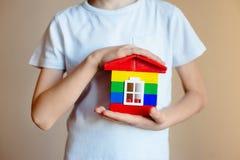 新房模型概念在孩子的手上 结构上大厦概念我的私有项目 银行贷款 抵押 免版税库存图片