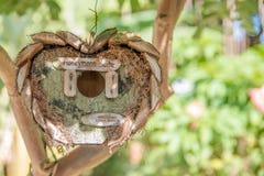 新房-木鸟树上小屋在形状的庭院里  库存图片