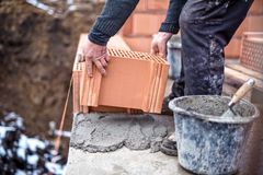 新房建造场所,工作者修筑有修平刀的砖墙,水泥和灰浆 免版税图库摄影