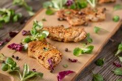 新新近地油煎的可口切片在一个木板的肉用新鲜的草本 在一个木板的开胃牛排 仍然1寿命 图库摄影