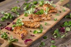 新新近地油煎的可口切片在一个木板的肉用新鲜的草本 在一个木板的开胃牛排 仍然1寿命 免版税库存图片