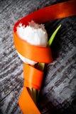新春天郁金香关闭与在老灰色woode的橙色丝带 图库摄影