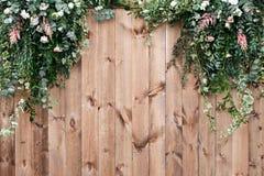 新春天绿化与在木篱芭背景的白花和叶子植物 免版税库存照片