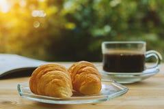 新月形面包、一杯咖啡和被打开的书 免版税库存图片
