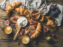 新月形面包、乳清干酪乳酪、无花果、新鲜的莓果、熏火腿、蜂蜜和浓咖啡 免版税图库摄影